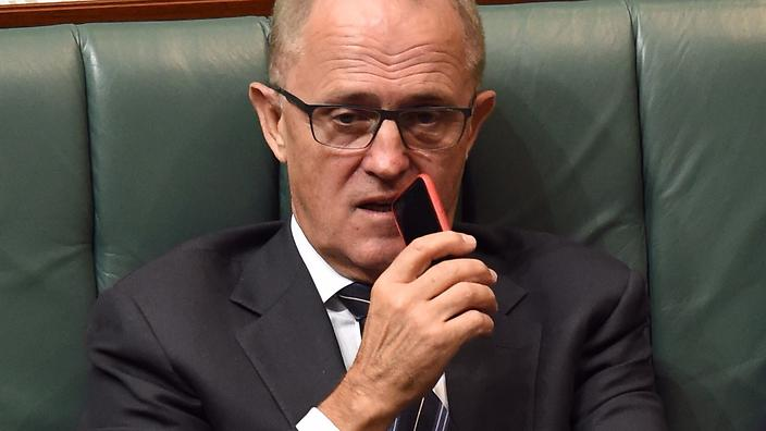 Communications minister Malcolm Turnbull holds his mobile phone up to his mouth as he listens and watches Question Time from the frontbench in the house of representatives at Parliament House in Canberra, Monday, Feb. 23, 2015. (AAP Image/Mick Tsikas) NO ARCHIVING