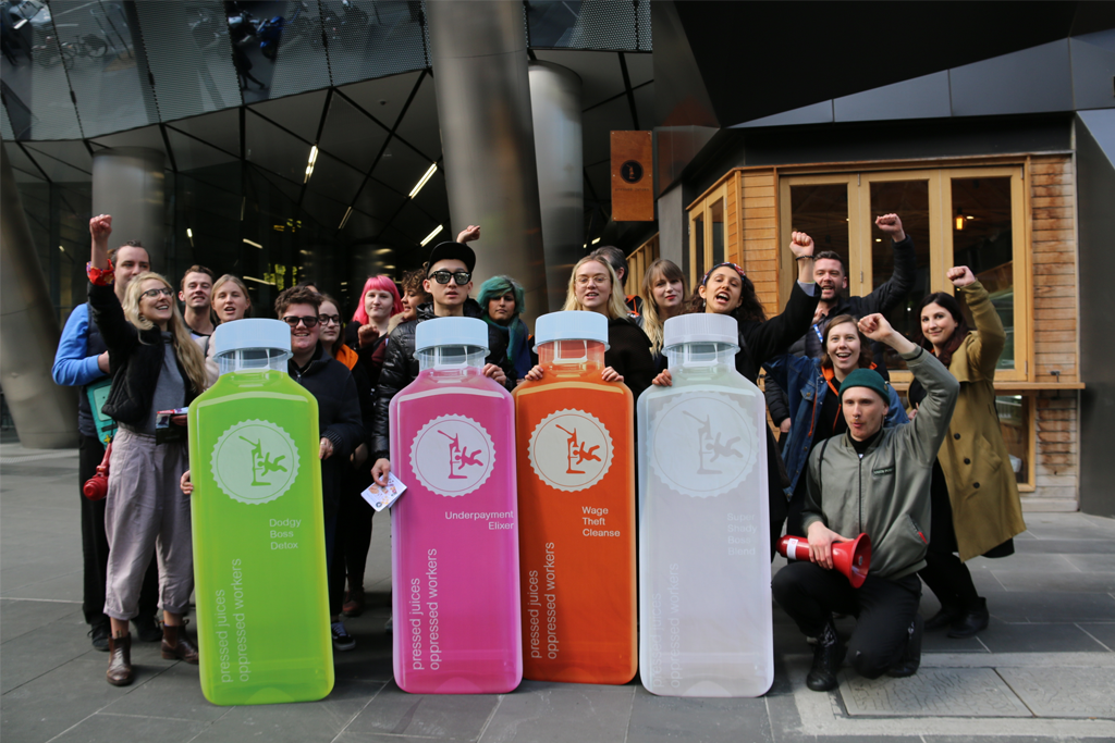 Pressed Juices workers rally outside a store to protest wage theft.